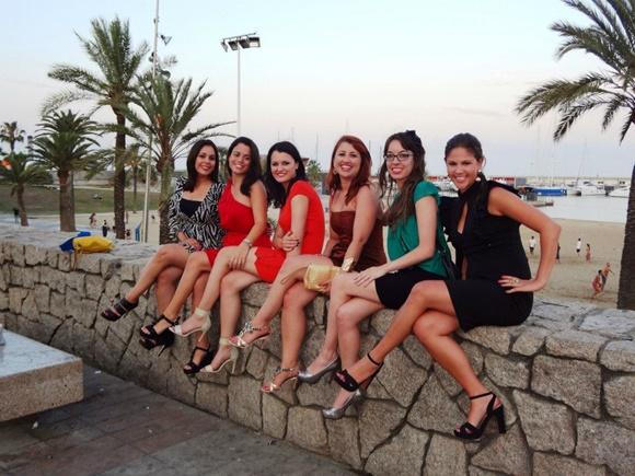 Érika e amigas sentadas na mureta diante da boate, em frente à praia Blog Vem Por Aqui