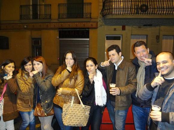 Érika e amigos fazendo sinal de silêncio com dedo na boca em frente ao bar Blog Vem Por Aqui