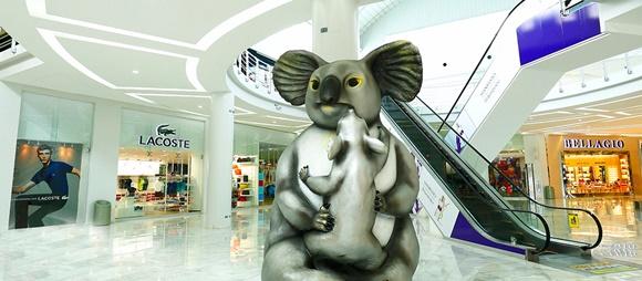 Lojas com escada rolante no meio e estátua de um coala carregando um filhote no colo Blog Vem Por Aqui
