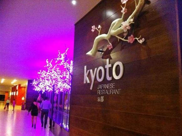 Entrada do restaurante japonês com parede de madeira com letreiro escrito Kyoto e galho simulando cerejeira, ao lado luz roxa com árvores iluminadas também simulando cerejeiras Blog Vem Por Aqui