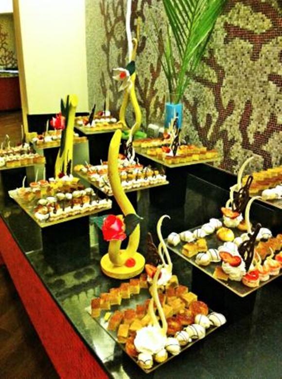 Mesa com vários pratos quadrados cheios de doces em diferentes formatos Blog Vem Por Aqui