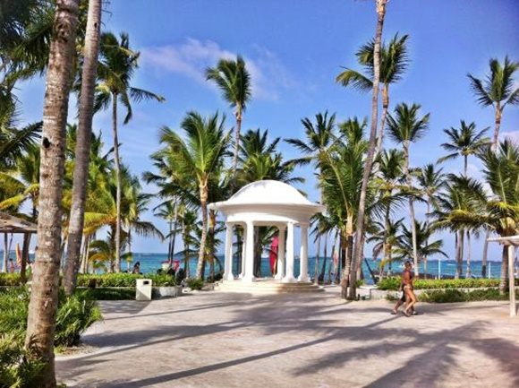 Área central com pequeno coreto redondo, palmeiras dos lados e mar ao fundo Blog Vem Por Aqui