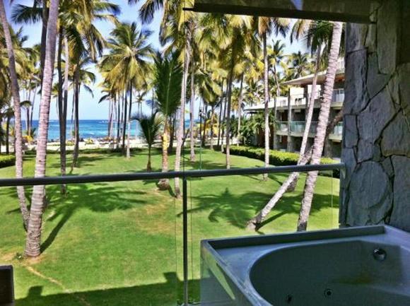 Varanda do quarto com vista para o gramado com palmeiras e mar ao fundo, na lateral, parede de pedra e banheira Blog Vem Por Aqui