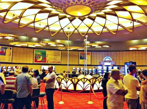 Pessoas na entrada do cassino com mesa de vidro no meio e cordas separando o público dessa mesa Blog Vem Por Aqui