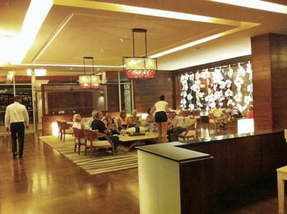 Bar do lobby com pessoas em volta de uma mesa e garçonete no meio, servindo Blog Vem Por Aqui