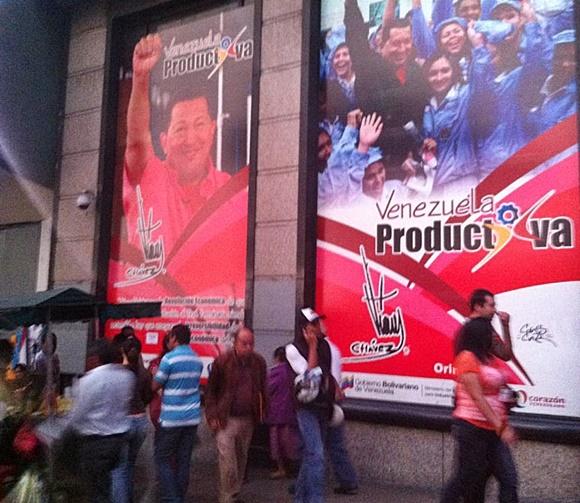 Pessoas andando nas ruas diante de dois cartazes gigantes do governo, o primeiro com Chavez de mão levantada e punho cerrado e o segundo dele no meio de adolescentes Blog Vem Por Aqui