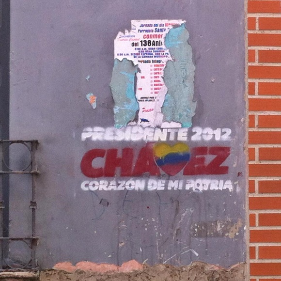 Parede descascada com cartaz se desfazendo e abaixo pintura dizendo 'Presidente 2012, Chavez, Corazón de Mi Patria' Blog Vem Por Aqui
