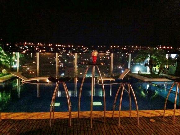 Mesas altas e cadeiras em frente à piscina e, ao fundo, parede de vidro com vista para as luzes da cidade Blog Vem Por Aqui