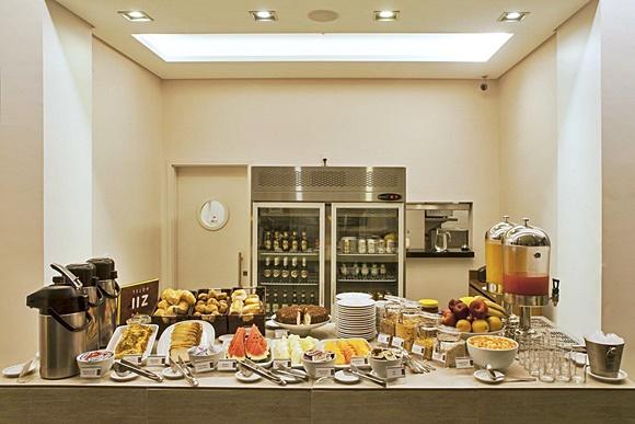 Balcão com itens do café, garrafas térmicas, pratos com frutas e bolos e filtros com sucos ao lado Blog Vem Por Aqui