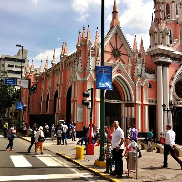 Igreja antiga no centro e pessoas atravessando a rua e na calçada Blog Vem Por Aqui