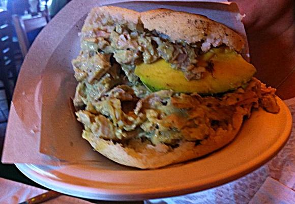 Arepa aberta, em cima de um prato com guardanapo de papel cinza, recheada com frango e abacate no meio Blog Vem Por Aqui
