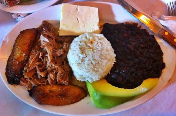 Prato de pavillón criollo com banana frita, carne assada, pedaço de queijo, arroz, feijão e tira de abacate Blog Vem Por Aqui