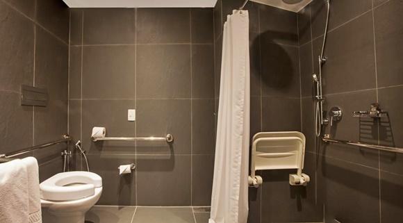 Banheiro adaptado com barras de ferro, box com cortina e cadeira Blog Vem Por Aqui