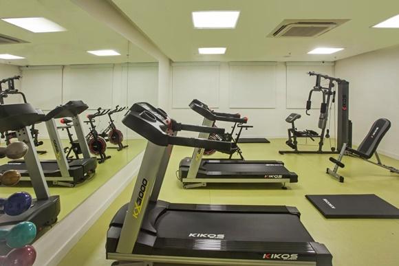 Academia do hotel com esteiras na frente, bicicletas ao lado e aparelhos de musculação atrás Blog Vem Por Aqui