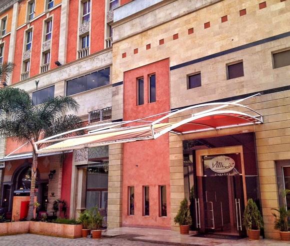 Fachada do hotel com toldo grande de metal e porta com letreiro acima Blog Vem Por Aqui