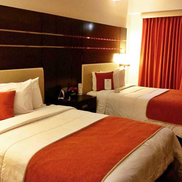 Quarto do hotel com duas camas e painel grande de madeira atrás Blog Vem Por Aqui