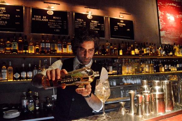 Barman colocando bebida em taça de drink Blog Vem Por Aqui