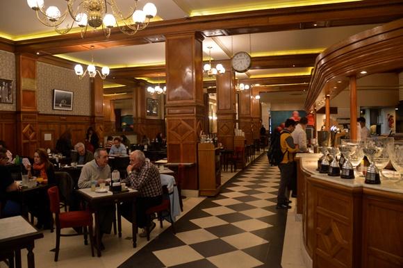Parte interna do café com pessoas nas mesas, piso tipo mosaico em preto e branco e balcão de madeira Blog Vem Por Aqui
