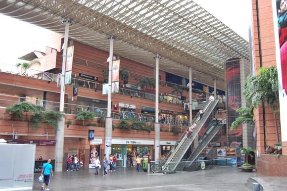 Área interna do shopping com escada rolante entre os andares e pessoas andando no piso de baixo Blog Vem Por Aqui