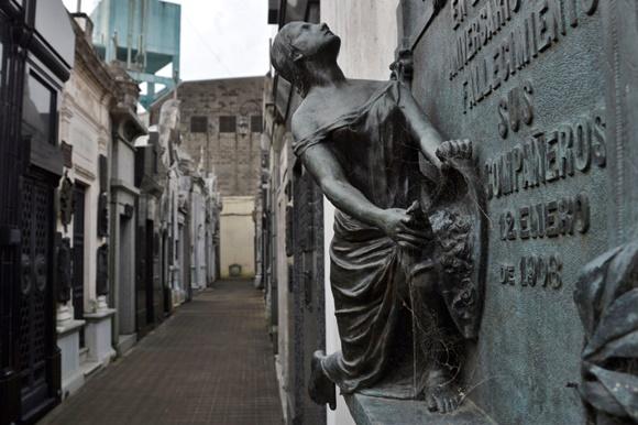Escultura de uma mulher ajoelhada e olhando para cima, sobre um túmulo num dos corredores do cemitério Blog Vem Por Aqui