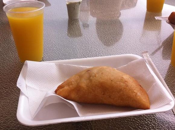 Bandeja de isopor com guardanapo e empanada em cima e copo de suco de laranja à frente Blog Vem Por Aqui