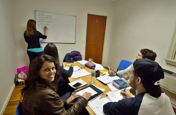 Glória na sala de aula sentada numa mesa com outros três colegas enquanto uma pessoa escreve no quadro Blog Vem Por Aqui