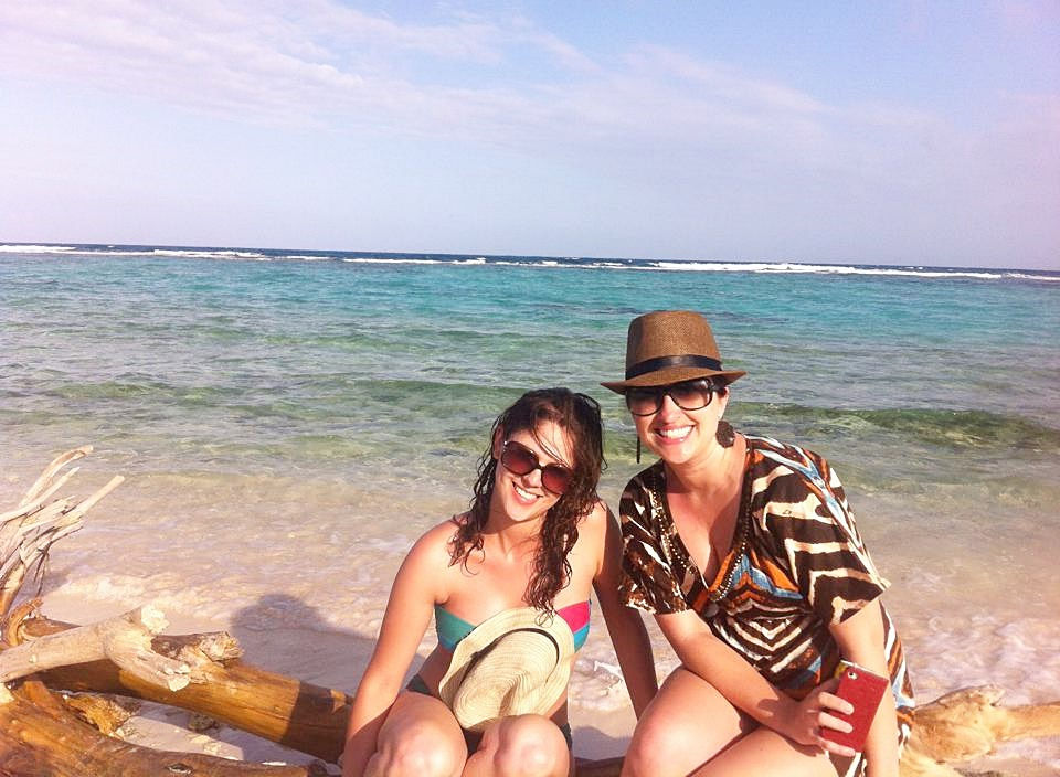 Diana e Érika sentadas num tronco de madeira diante do mar transparente Blog Vem Por Aqui