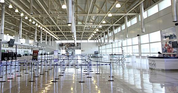 Saguão do aeroporto vazio com divisórias móveis para filas no meio e guichê para turistas no canto direito Blog Vem Por Aqui