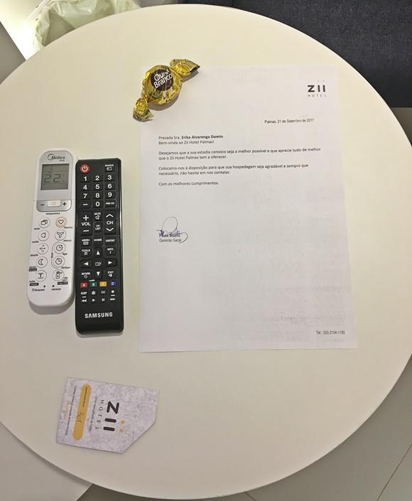 Mesinha com controles do ar e da TV, envelope para a chave do quarto e, no centro, carta de boas-vindas com um bombom Ouro Branco na ponta Blog Vem Por Aqui