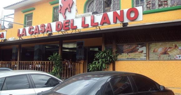 Fachada do restaurante com letreiro grande em vermelho com o nome e um homem montado num cavalo dando pinote em cima, na frente, carros parados Blog Vem Por Aqui