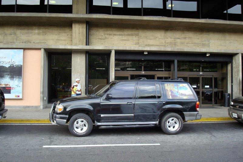 Carro preto em frente ao aeroporto Blog Vem Por Aqui