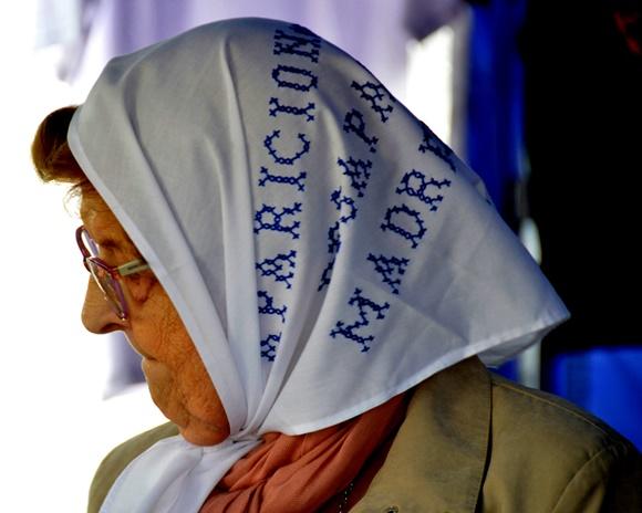 Senhora idosa, de óculos com lenço branco com palavras bordadas em azul na cabeça Blog Vem Por Aqui