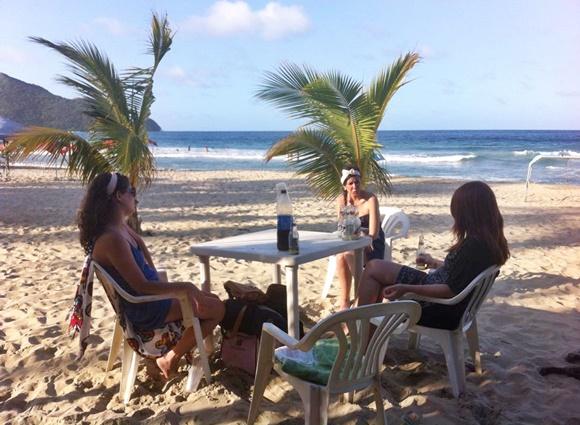 Diana e Érika de costas, sentadas numa mesa, com Nananda em frente e mar azul ao fundo Blog Vem Por Aqui
