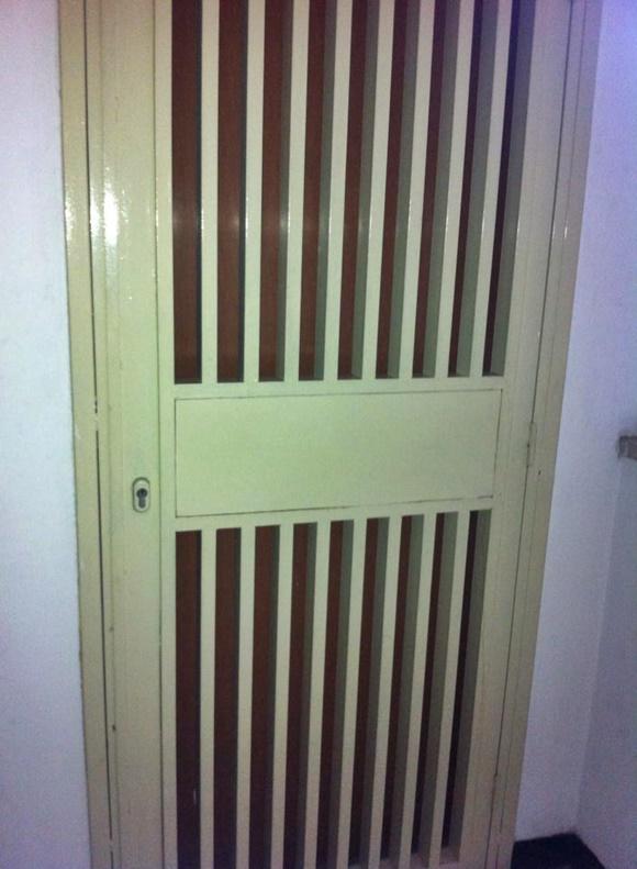 Porta de ferro gradeada em frente à porta de madeira Blog Vem Por Aqui