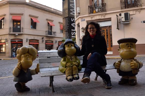 Glória sentada no banco com a estátua de Matilda ao lado e outros dois personagens do desenho, um de cada lado do banco Blog Vem Por Aqui