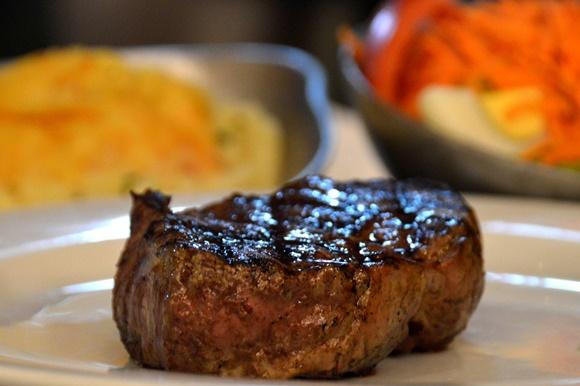 Bife alto de carne sobre um prato Blog Vem Por Aqui
