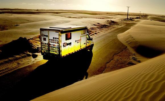 Motorhome passando numa estrada no meio de dunas de areia Blog Vem Por Aqui