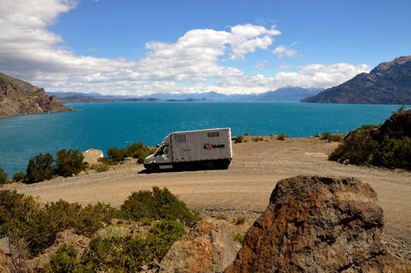 Motorhome parado numa estrada com o mar azul no fundo Blog Vem Por Aqui