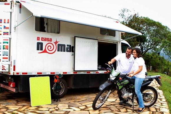 Glória em cima da moto e Renato ao lado, diante do motorhome, com a porta da 'garagem' aberta Blog Vem Por Aqui