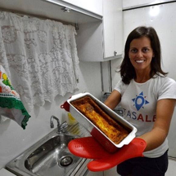 Glória com uma forma com bolo na mão, diante da pia da cozinha Blog Vem Por Aqui