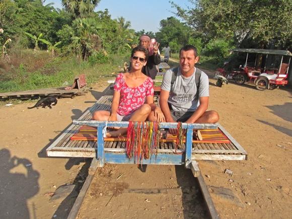 Casal sentado numa tábua de madeira que passa por trilhos e é empurrada por uma bicicleta, no Camboja Blog Vem Por Aqui
