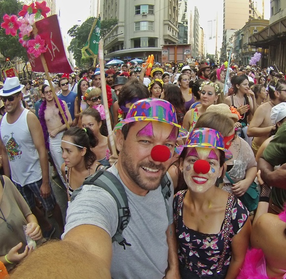 Renato e Glória, fantasiados de palhaço, em frente à multidão no meio de um bloco de carnaval do Rio Blog Vem Por Aqui