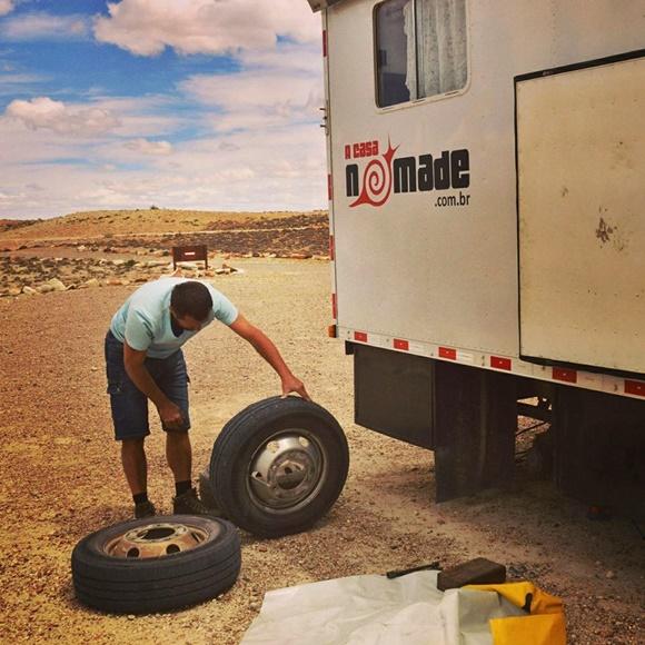 Renato curvado olhando para um pneu que está segurando e diante de outro no chão Blog Vem Por Aqui
