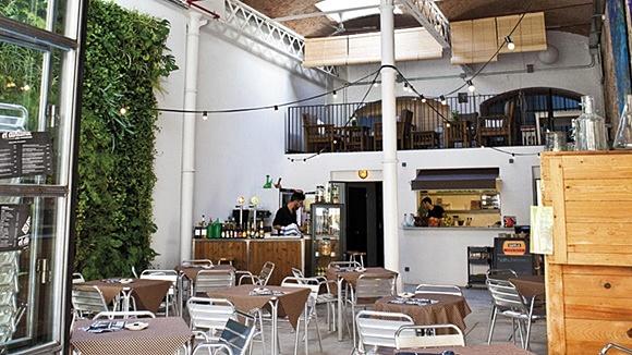 Pátio do Dinamic com parede de plantas, mesas no centro e pessoas trabalhando atrás do balcão no fundo. No alto, varais de luzes Blog Vem Por Aqui