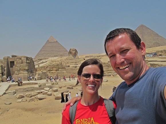 Casal abraçado, sorrindo, em frente às pirâmides de Gize, no Cario Blog Vem Por Aqui