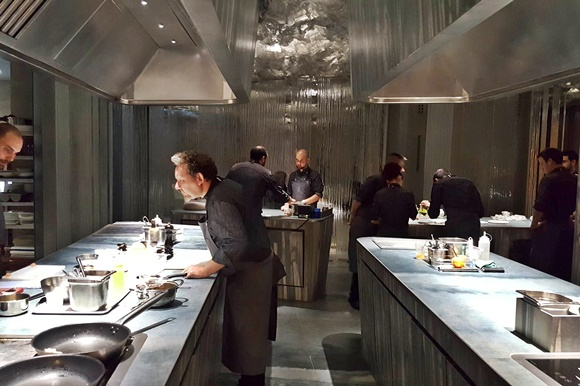 Cozinha aberta do Enigma com chefs vestidos de preto trabalhando no meio dela e no final Blog Vem Por Aqui