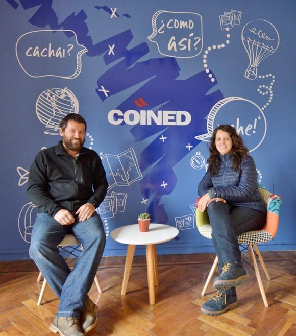 Renato e Glória sentados diante de um painel azul com expressões em espanhol e a sigla COINED no meio Blog Vem Por Aqui
