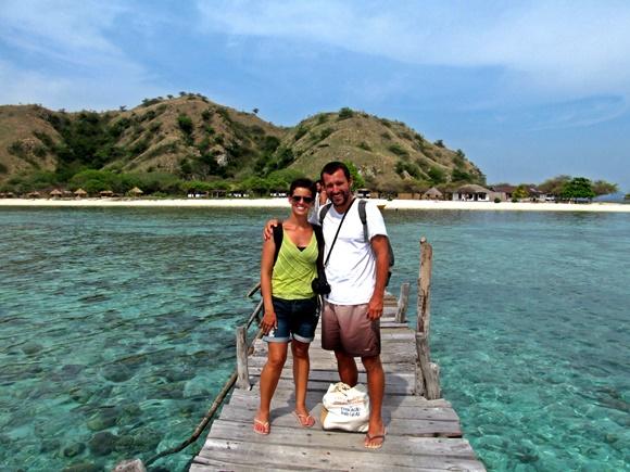 Renato e Glória em cima de um pequeno pier de madeira abraçados, cercados de mar azul transparente e com uma montanha ao fundo Blog Vem Por Aqui