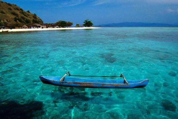 Canoa azul boiando no mar azul transparente com areia branca bem ao fundo Blog Vem Por Aqui
