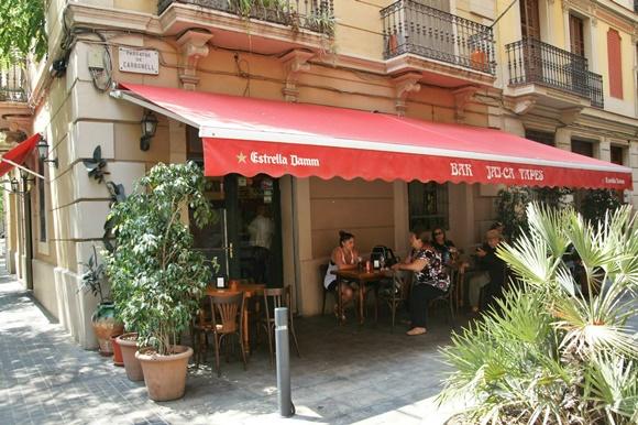 Mesas embaixo de toldo vermelho em frente ao bar Blog Vem Por Aqui